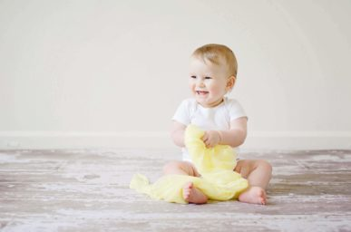 benefits of child adoption - picture of a baby playing and smiling | Minella Law
